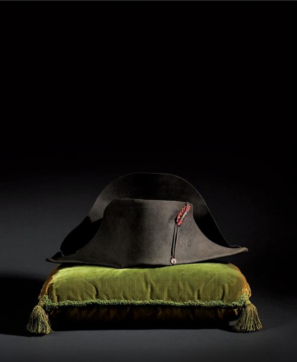 89 - Légendaire chapeau de l'empereur Napoléon Ier, de forme traditionnelle dite à la française, en feutre dit en castor noir, orné: - d'une cocarde blanche, bleue et rouge au centre, (refaite postérieurement), - d'une simple ganse de soie noire - et d'un reste de bouton en bois dont la garniture n'est plus. Ce bouton était d'origine recouvert de soie ou de crins noirs. La partie supérieure de l'aile de devant est renforcée à l'intérieur par une pièce cousue de feutre noir de 16,5 cm de long sur 3 cm de large, comme le sont tous les chapeaux de l'Empereur. Cette pièce de renfort permettant la prise en main ainsi que la bonne tenue. Ce chapeau a conservé sa coiffe intérieure (ce qui est particulièrement rare). Elle est en soie matelassée gris-vert, à trois piqûres concentriques dans le fond et des piqûres longitudinales sur les côtés. Sans cuir sur le pourtour (l'Empereur ne le supportait pas). Longueur: 49 cm. Hauteur aile arrière: 20,7 cm. Hauteur aile avant: 15 cm. Diamètre intérieur: 56 cm. B.E. d'usage, importantes traces de port (quelques petites déchirures, bordure intérieure avant usée, petit manque à la coiffe intérieure). 300 000/400 000 € Provenance: - Joseph Giraud, vétérinaire de la Maison de l'Empereur. - Par succession, famille Loir, puis famille Claitte. - Vente aux enchères des Souvenirs de Giraud, vétérinaire en chef des Ecuries de la Maison de l'empereur, le 3 juin 1926 (Maitre Albinet, expert Pierre Foury), n°78, Vendu 51 836 francs. ( La trousse de vétérinaire et des brevets lui ayant appartenu étaient également dispersés). - Musée napoléonien de Monaco.